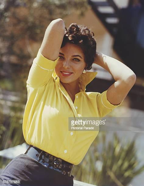English actress Joan Collins wearing a yellow blouse circa 1960