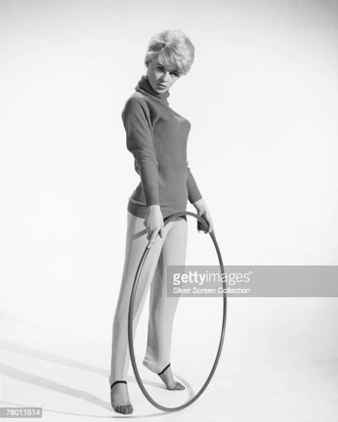 English actress Julie Christie holding a hula hoop circa 1963