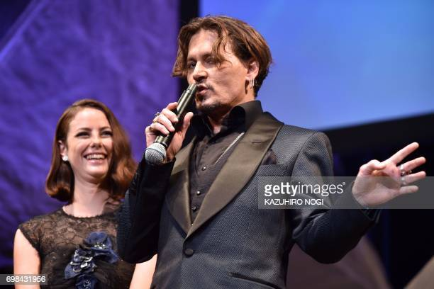 English actress Kaya Scodelario laughs as US actor Johnny Depp holds the microphone upsidedown during a promotional event for the film 'Pirates of...