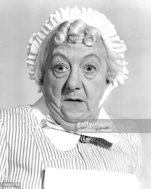 English actress Margaret Rutherford wearing a maid's housecoat and bonnet circa 1960
