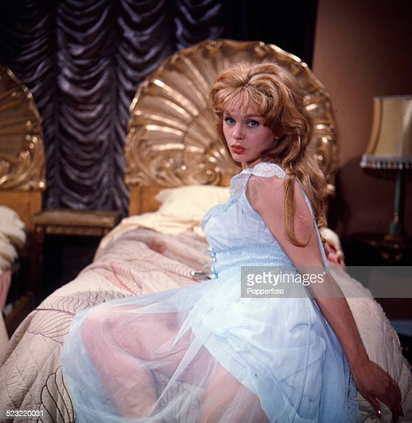 English actress Sally Smith posed wearing a pastel blue negligee and lying on a bed on the set of the film Father Came Too In 1963