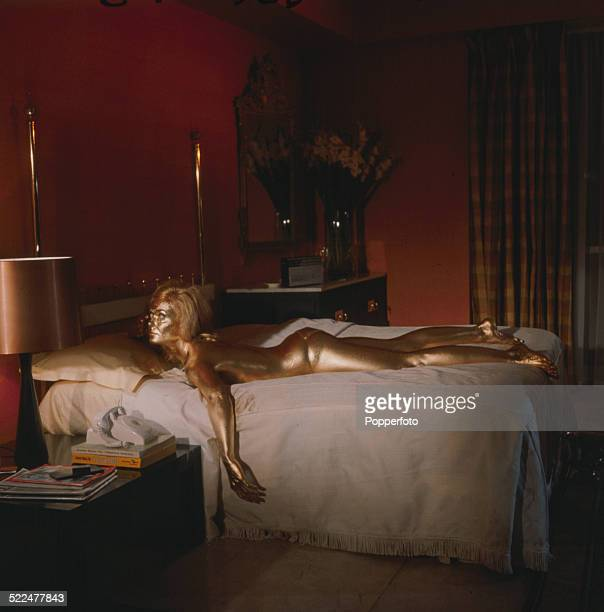 English actress Shirley Eaton pictured in character as Jill Masterson lying on a bed covered in gold paint in a scene from the James Bond film...