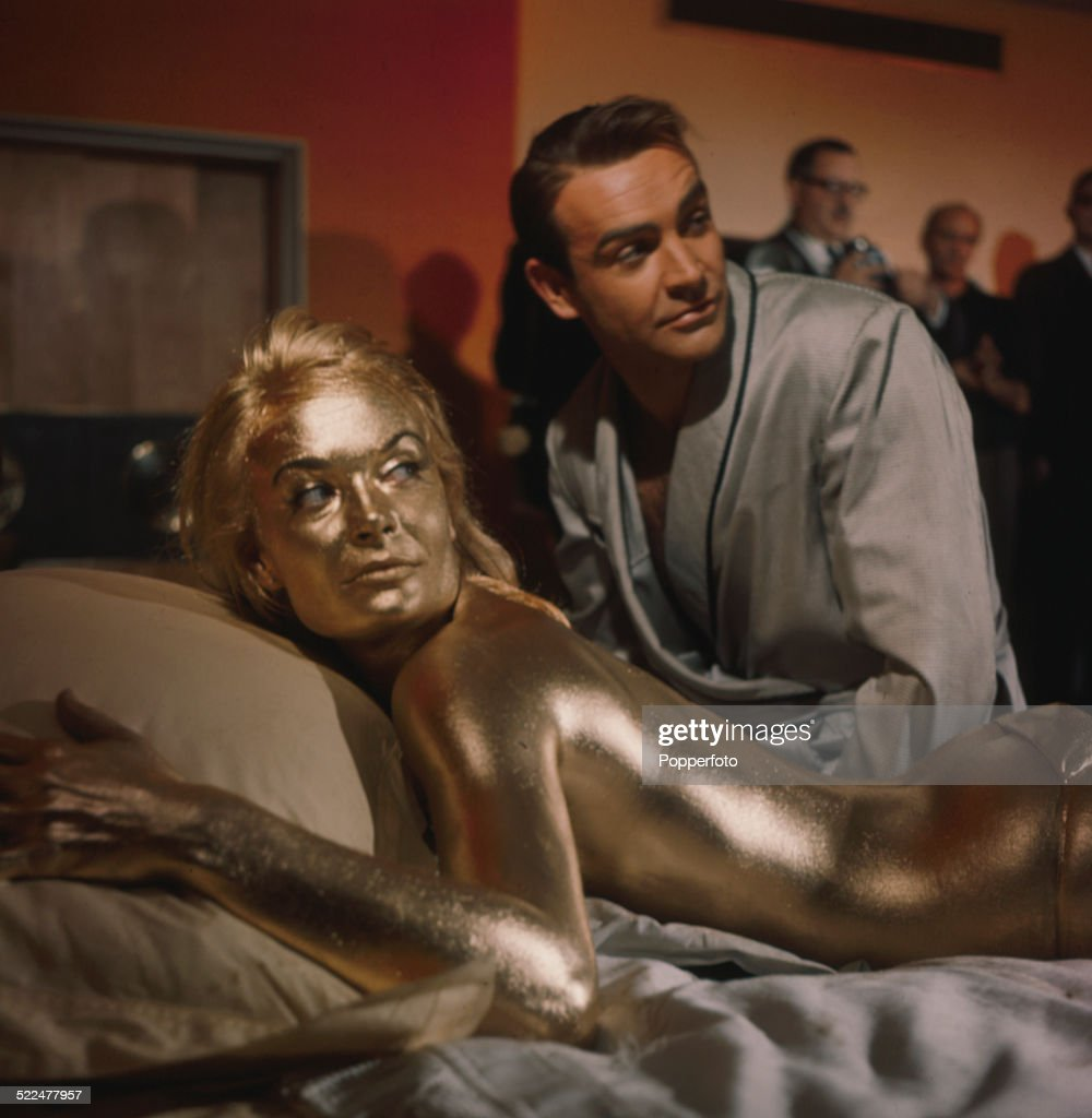 English actress <a gi-track='captionPersonalityLinkClicked' href=/galleries/search?phrase=Shirley+Eaton&family=editorial&specificpeople=900615 ng-click='$event.stopPropagation()'>Shirley Eaton</a> pictured in character as Jill Masterson, lying on a bed covered in gold paint next to actor <a gi-track='captionPersonalityLinkClicked' href=/galleries/search?phrase=Sean+Connery&family=editorial&specificpeople=201589 ng-click='$event.stopPropagation()'>Sean Connery</a> on the set of the James Bond film 'Goldfinger' in 1964.