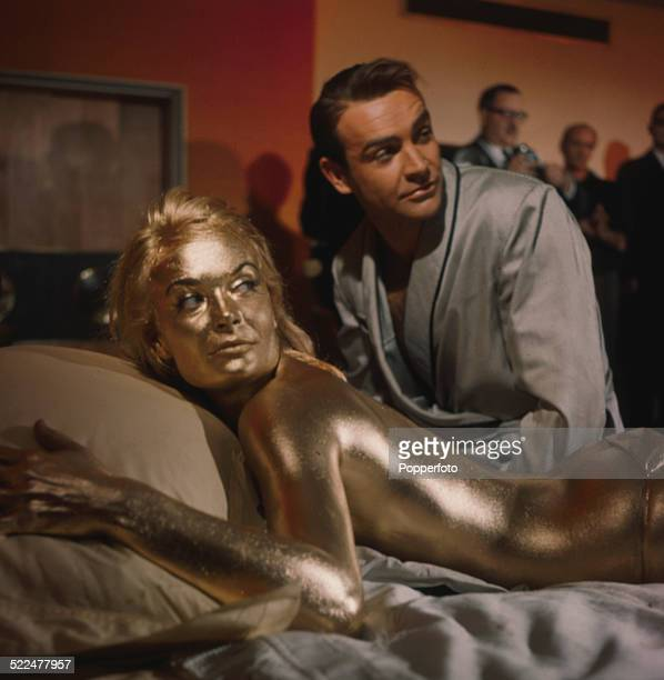 English actress Shirley Eaton pictured in character as Jill Masterson lying on a bed covered in gold paint next to actor Sean Connery on the set of...