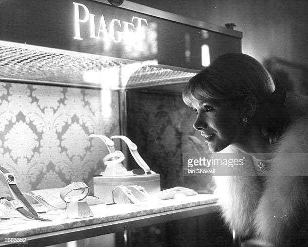 English actress Susan Hampshire looks at an exhibition case containing Piaget watches at Asprey's of Bond Street London