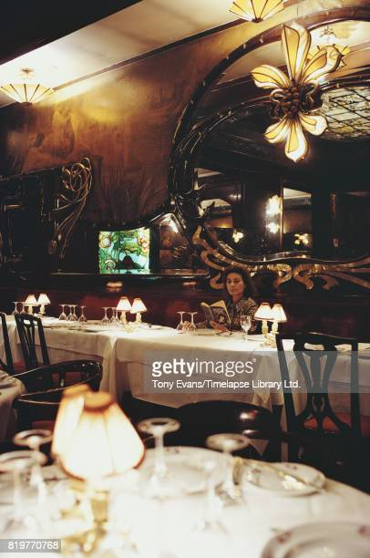English actress Yvonne Mitchell reading a book at Maxim's restaurant in Paris France 1972