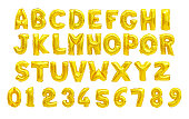 English alphabet and numerals from yellow (Golden) balloons on a white background. holidays and education