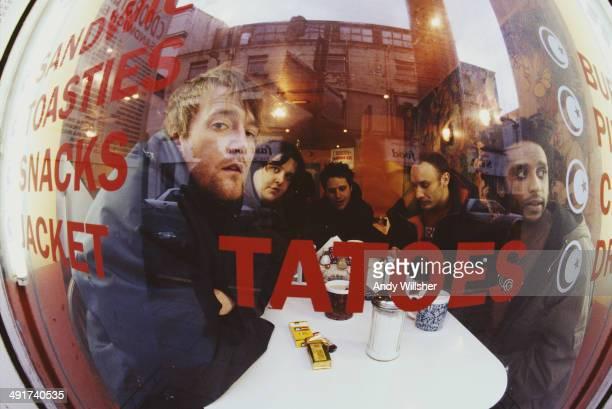English alternative rock Elbow seen through a cafe window December 2000 Left to right singer Guy Garvey keyboard player Craig Potter guitarist Mark...