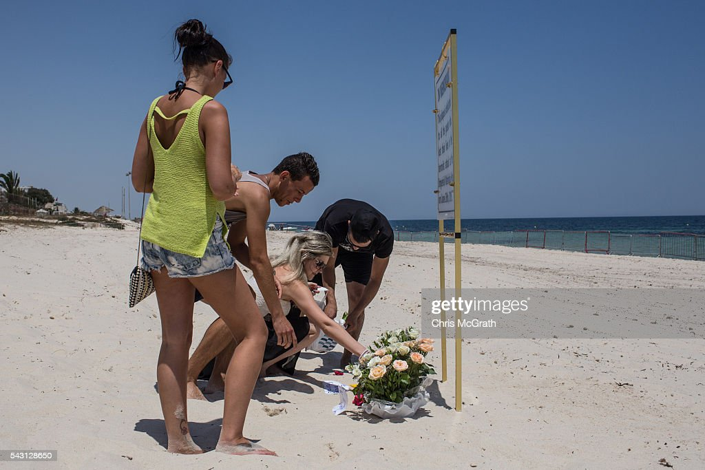 English and Tunisian tourists lay flowers for the victims of the 2015 Sousse Beach terrorist attack at a memorial sign on the beach in front of the Imperial Marhaba hotel on June 26, 2016 in Sousse, Tunisia. Today marks the one year anniversary of the Sousse Beach terrorist attack, which killed 38 people including 30 Britons. Before the 2011 revolution, tourism in Tunisia accounted for approximately 7% of the country's GDP. The two 2015 terrorist attacks at the Bardo Museum and Sousse Beach saw tourism numbers plummet even further forcing hotels to close and many tourism and hospitality workers to lose their jobs.