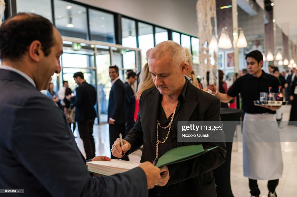 English artist <a gi-track='captionPersonalityLinkClicked' href=/galleries/search?phrase=Damien+Hirst&family=editorial&specificpeople=215142 ng-click='$event.stopPropagation()'>Damien Hirst</a>'s signs the catalogue of Relics Exhibition at Al Riwaq space next to Doha's Museum of Islamic Art on October 9, 2013 in Doha, Qatar.