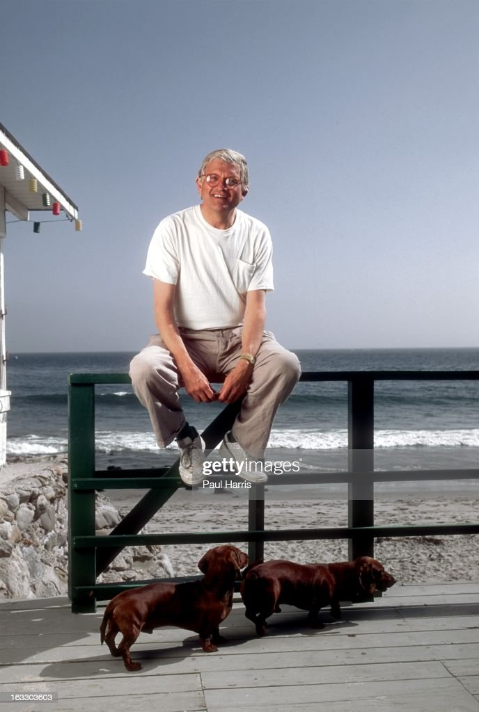 English artist David Hockney poses for a portrait with his dogs on the terrace of his beach house in April 1991 in Malibu California