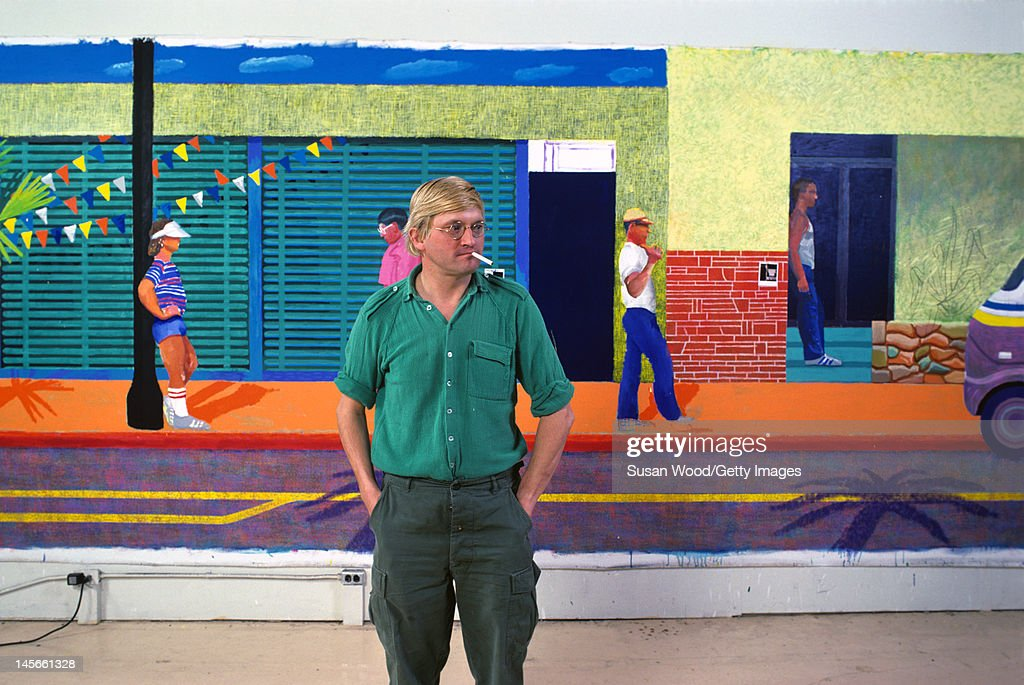 English artist David Hockney poses in front of a large painting of a street scene in his studio 1980