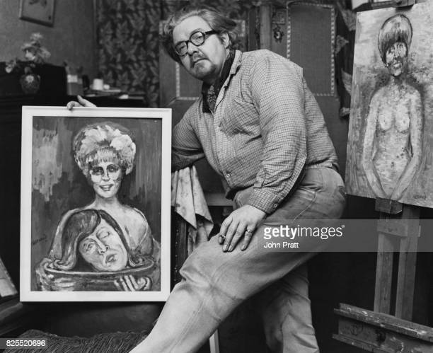 English artist James Lawrence Isherwood at home in Wigan UK with his paintings of Dusty Springfield as Salome bearing the head of John Lennon on a...