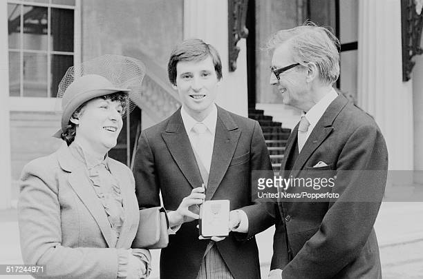 English athlete and middle distance runner Sebastian Coe pictured holding his MBE with his parents Peter Coe and Tina Coe at an Investiture at...