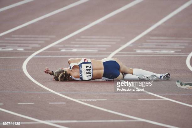 English athlete Paula Radcliffe collapses on the track after crossing the finish line in fourth place for Great Britain in the final of the Women's...