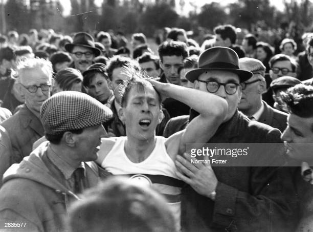 English athlete Roger Bannister amongst a crowd at Oxford after becoming the first person in the world to run a mile in under 4 minutes