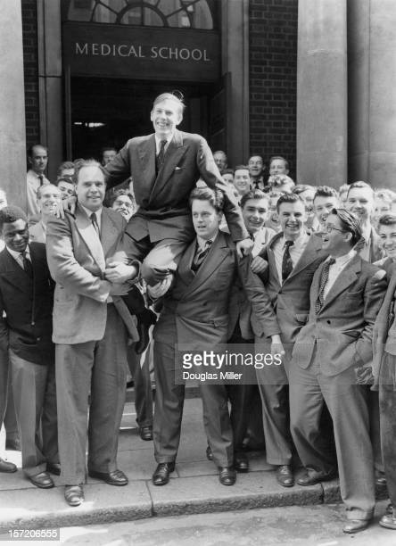 English athlete Roger Bannister is chaired by his fellow medical students at St Mary's Hospital Paddington the day after he ran his recordbreaking...
