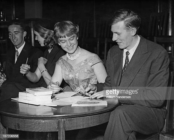 English athlete Roger Bannister signs a pound note for sponsor Amanda Legge at County Hall London 11th July 1955 Bannister is helping to launch a...