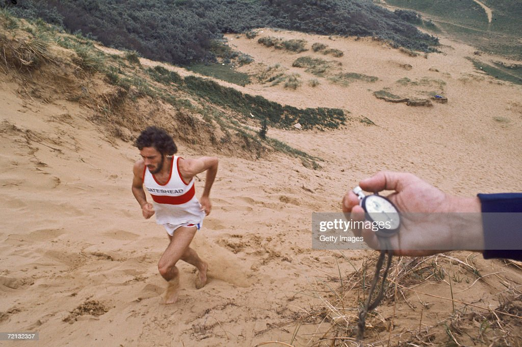 English athlete Steve Ovett training on a sand dune, under the supervision of his coach Harry Wilson, circa 1980.