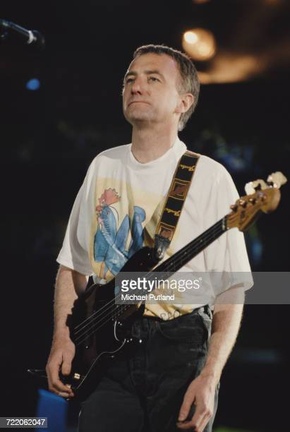 English bass guitarist John Deacon of rock group Queen performs live onstage with the band at the Freddie Mercury Tribute Concert at Wembley Stadium...