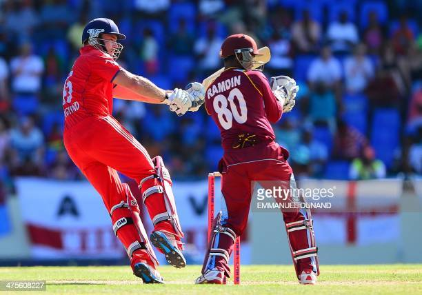 English batsman Michael Lumb plays a ball in front of West Indies wicketkeeper Dinesh Ramdin during the first One Day International match bewteen...