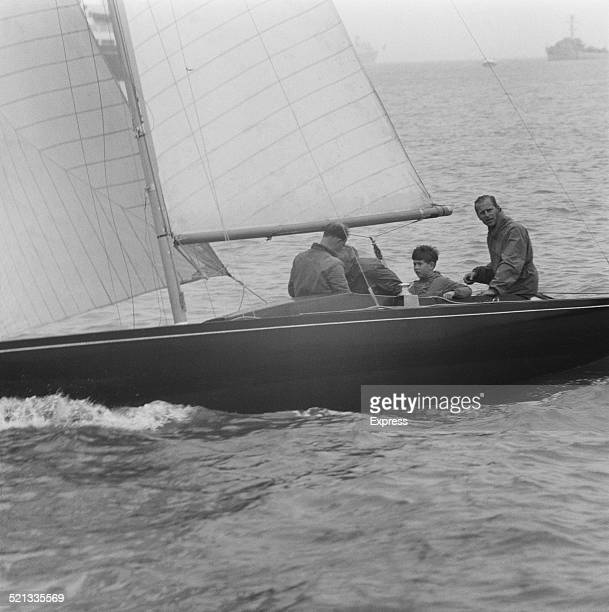 English boat designer Uffa Fox sailing at Cowes with Prince Philip Duke of Edinburgh and Charles Prince of Wales Isle of Wight 1958