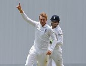 English bowler Joe Root celebrates with Jos Buttler after taking the wicket of Shiv Chanderpaul by lbw on day five of the first cricket Test match...