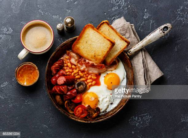 English Breakfast in cooking pan with fried eggs, sausages, bacon and beans
