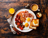 Full English breakfast with fried eggs, sausages, bacon, beans, toasts and coffee on wooden background