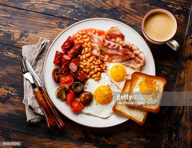 English breakfast with fried eggs, sausages, bacon, beans, toasts and coffee on wooden background