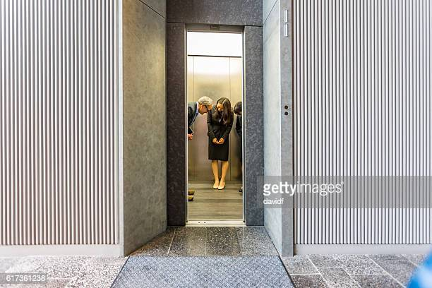 English Businessman With Japanese Corporate Professional Women in Office Elevator