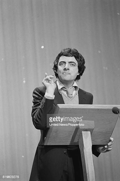 English comedian and actor Rowan Atkinson performs at a lectern on stage at the Palladium in London during rehearsals prior to his performance on the...