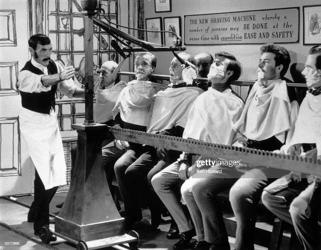 English comedian Eric Sykes (1923 - 2012, left) reviving the 'mass shaving machine', a nineteenth century invention, which can shave a dozen men at the same time, on an untransmitted pilot show for a proposed television series called 'Brainwaves', 28th October 1960. The series, in which unusual inventions from the 19th century were recreated, was never broadcast.