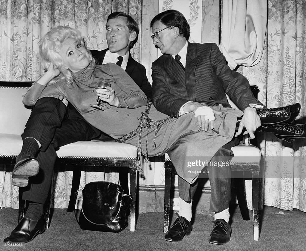 English comic actor and comedian Kenneth Williams and English comedy actor and musician Charles Hawtrey holding English actress Barbara Windsor at a...