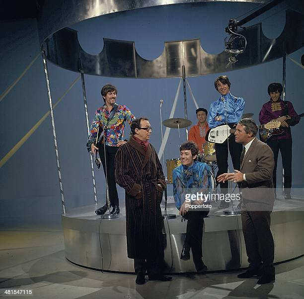1968 English comic duo Eric Morecambe and Ernie Wise of Morecambe and Wise stand with pop group The Hollies on their television series 'The Morecambe...