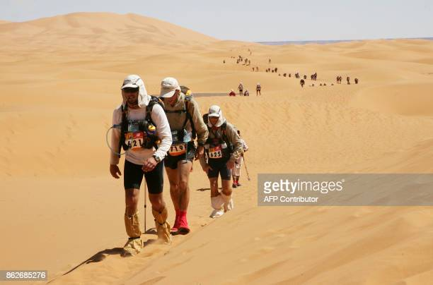 English competitors Daid Cassidy Clyde Luddington Mark Chase crosse the dunes of Chebbi some 22kms to reach the finish line of the Marathon des...