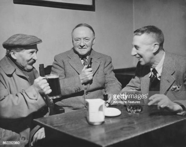 English composer and author Sir Arnold Bax Master of the King's Music enjoys a lunchtime drink at the White Horse Hotel in Storrington Sussex with...