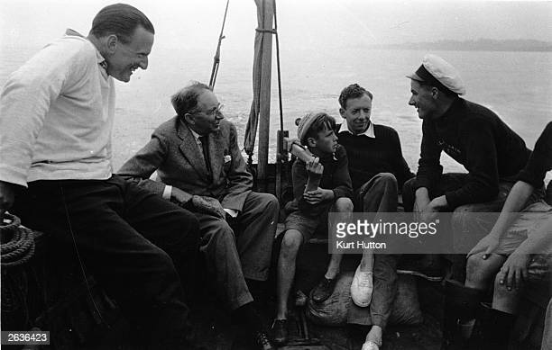 English composer Benjamin Britten with a boy on his lap at sea with novelist Edward Morgan Forster second from left and tenor Sir Peter Pears left...