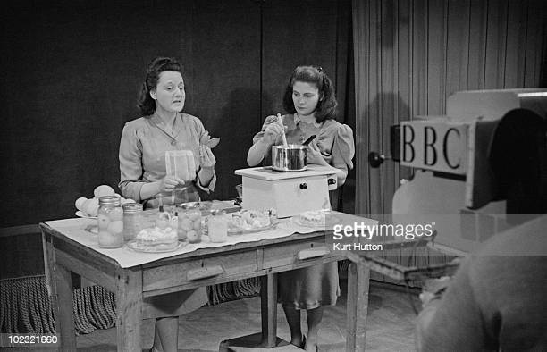 English cookery expert Marguerite Patten supervises pianist Geraldine Peppin as she stirs a pan on the BBC television show 'Designed For Women' April...