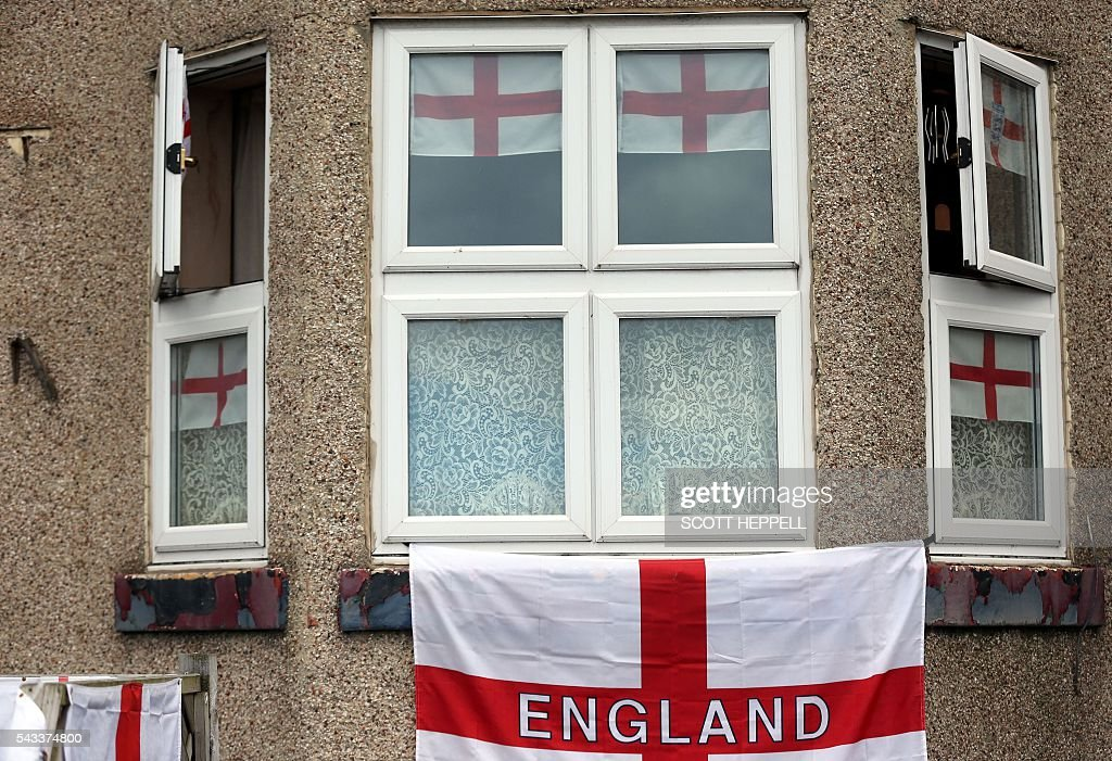 English Cross of St George flags hang adorn a house in Redcar, north east England on June 27, 2016 Thursday's dramatic vote to quit the European Union was driven by millions of people in the post-industrial north and centre of England, in working-class towns like Redcar, on the northeast coast. The strength of feeling may have stunned metropolitan Britain, but came as no surprise in places like Redcar, where 66.2 percent ultimately voted to leave the EU. / AFP / Scott Heppell
