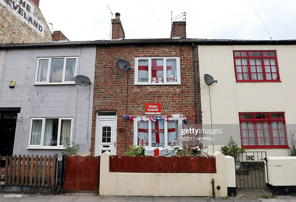 English Cross of St George flags hang in the windows and a 'Vote Leave' poster is displayed on a house in Redcar, north east England on June 27, 2016 Britain's historic decision to leave the 28-nation bloc has sent shockwaves through the political and economic fabric of the nation. It has also fuelled fears of a break-up of the United Kingdom with Scotland eyeing a new independence poll, and created turmoil in the opposition Labour party where leader Jeremy Corbyn is battling an all-out revolt. / AFP / Scott Heppell