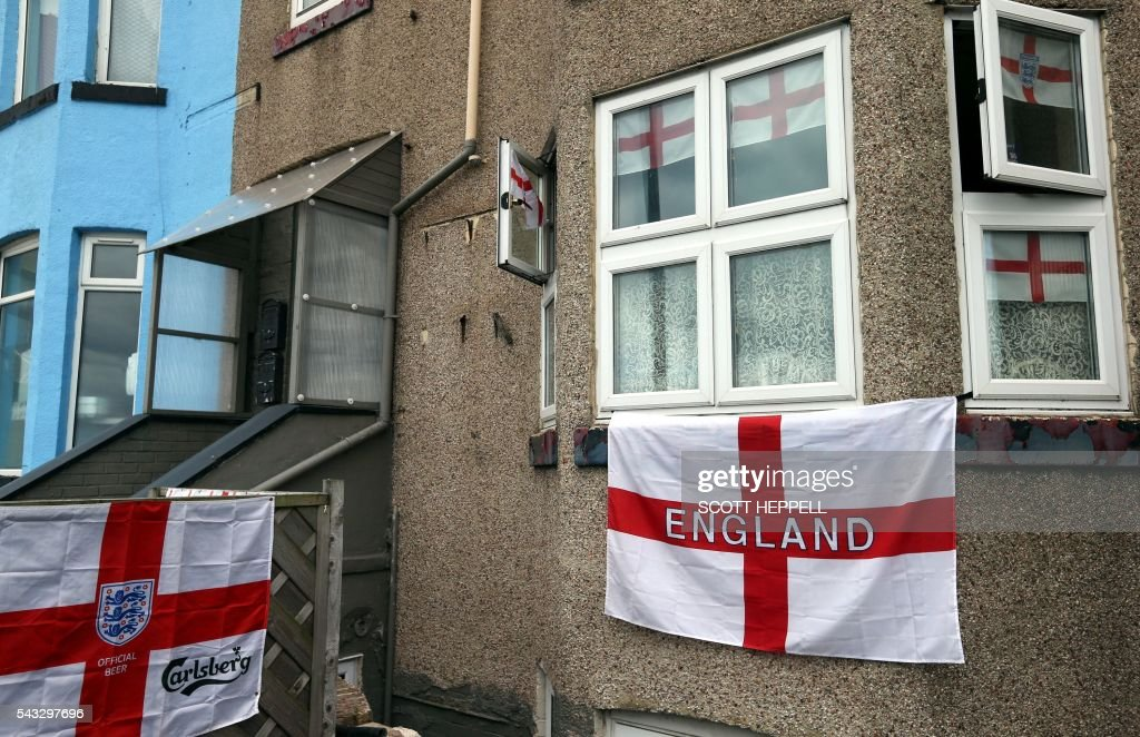 English Cross of St George flags hang outside a house in Redcar, north east England on June 27, 2016 Britain's historic decision to leave the 28-nation bloc has sent shockwaves through the political and economic fabric of the nation. It has also fuelled fears of a break-up of the United Kingdom with Scotland eyeing a new independence poll, and created turmoil in the opposition Labour party where leader Jeremy Corbyn is battling an all-out revolt. / AFP / Scott Heppell