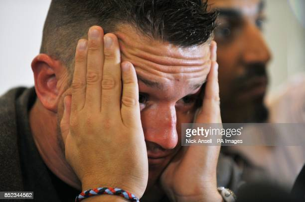English Defence League leader Tommy Robinson holds his head in his hands during a press conference at the Montague Hotel central London as he...