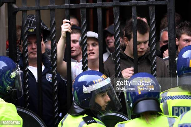 English Defence League supporters are herded into a pub entrance following a demonstration in Birmingham