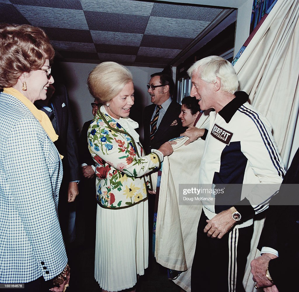 English disc jockey and television presenter Jimmy Savile (1926 - 2011) meets the Duchess of Kent in Jersey, November 1980.