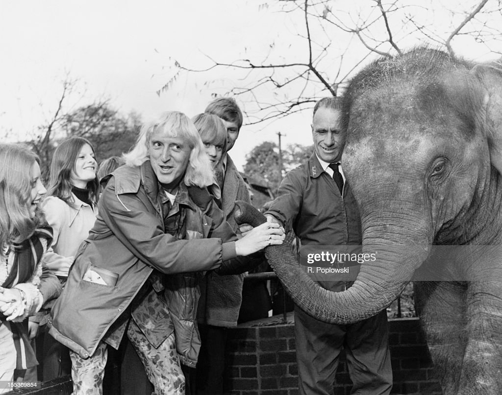 English disc jockey and television presenter Jimmy Savile (1926 - 2011) with one of the elephants at London Zoo, where he spent the day with young people from the Association of Youth Clubs, 5th November 1973.