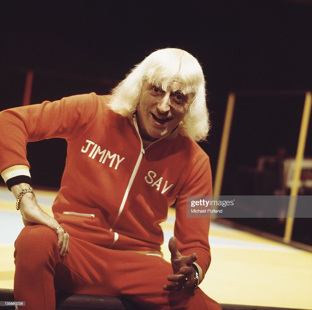English disc jockey Jimmy Savile (1926 - 2011) presenting the BBC music chart show 'Top Of The Pops', UK, circa 1973. He is wearing a personalised tracksuit.