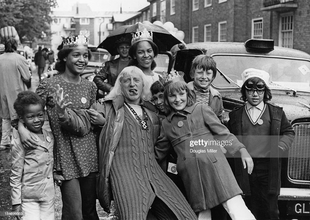 English dj and television presenter Jimmy Savile (1926 - 2011) joins a group of under-privileged and disabled children on a day out to Southend, organized by London taxi drivers, Beaumont Square, London, 7th August 1973.