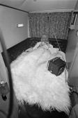 English dj and television presenter Jimmy Savile watching TV in bed in his motor home 31st December 1969