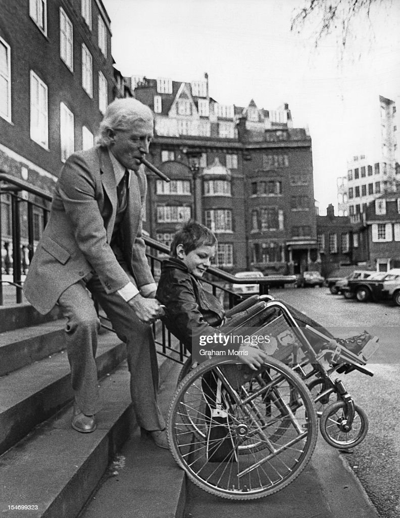 English dj and television presenter Jimmy Savile (1926 - 2011) with a former patient at Stoke Mandeville Hospital, 23rd January 1980. Savile has just launched a ten million-pound appeal for the hospital.